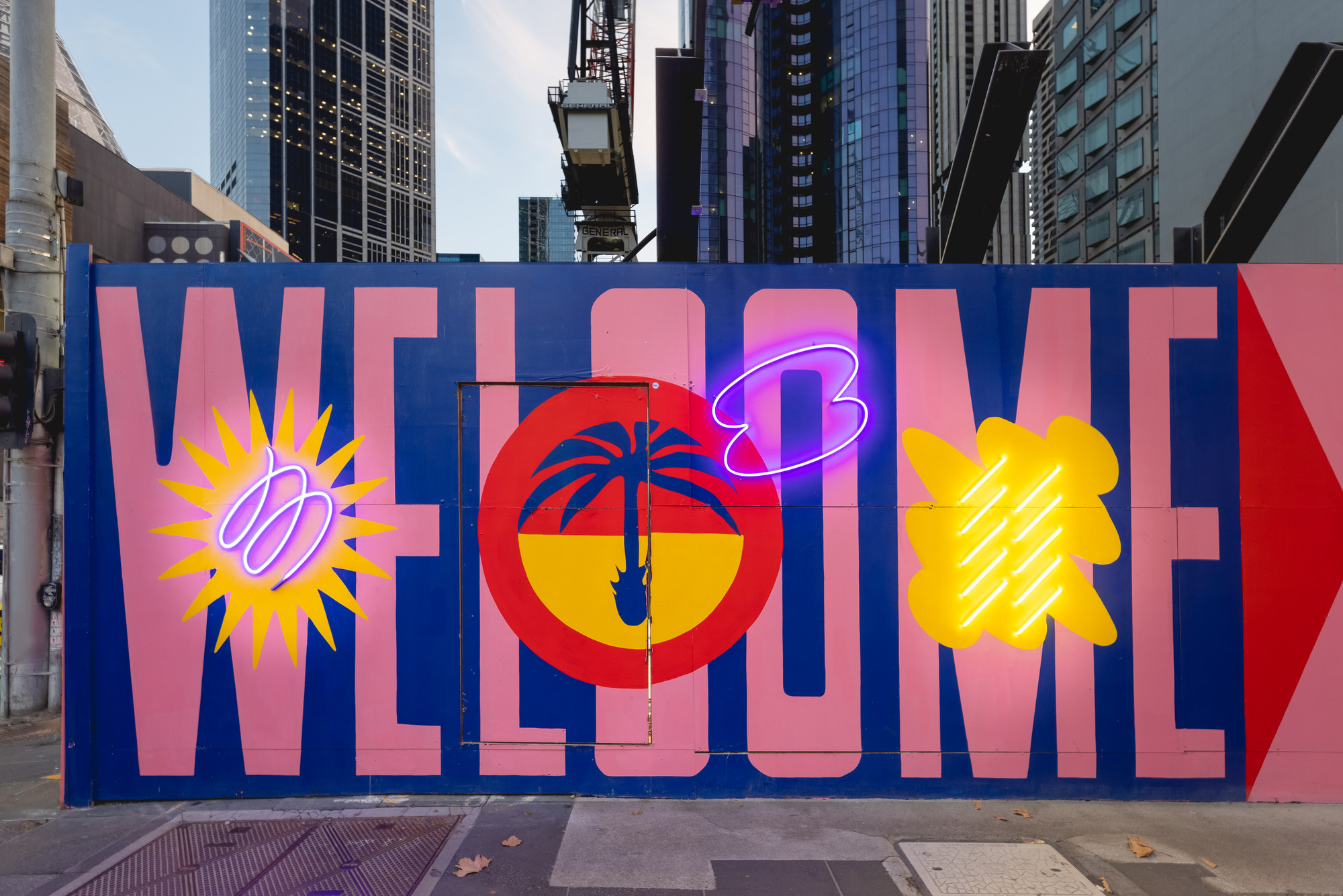 Artwork on a temporary construction fence says 'welcome' with neon lights in front of skyscrapers