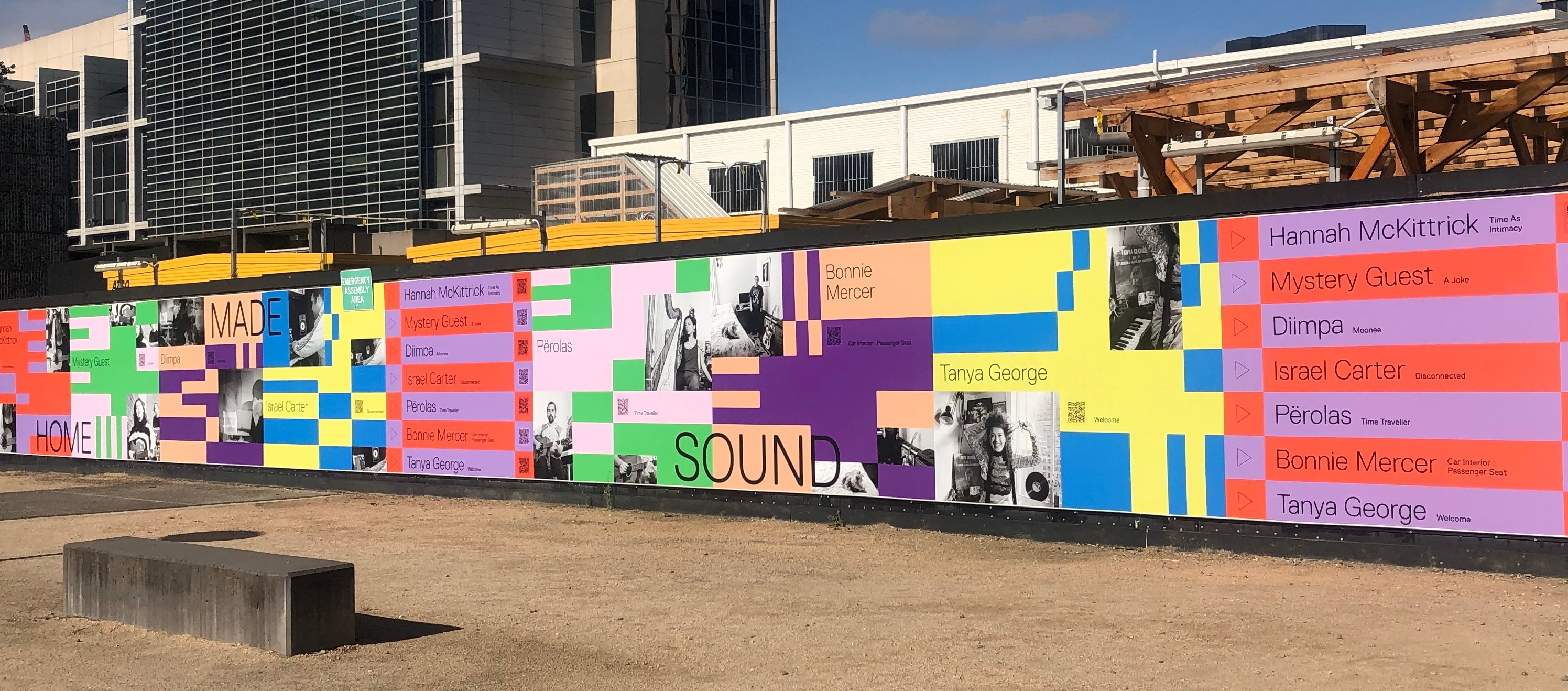 A mural featuring images of musicians and blocks of colours covers construction hoarding in a dusty plaza.
