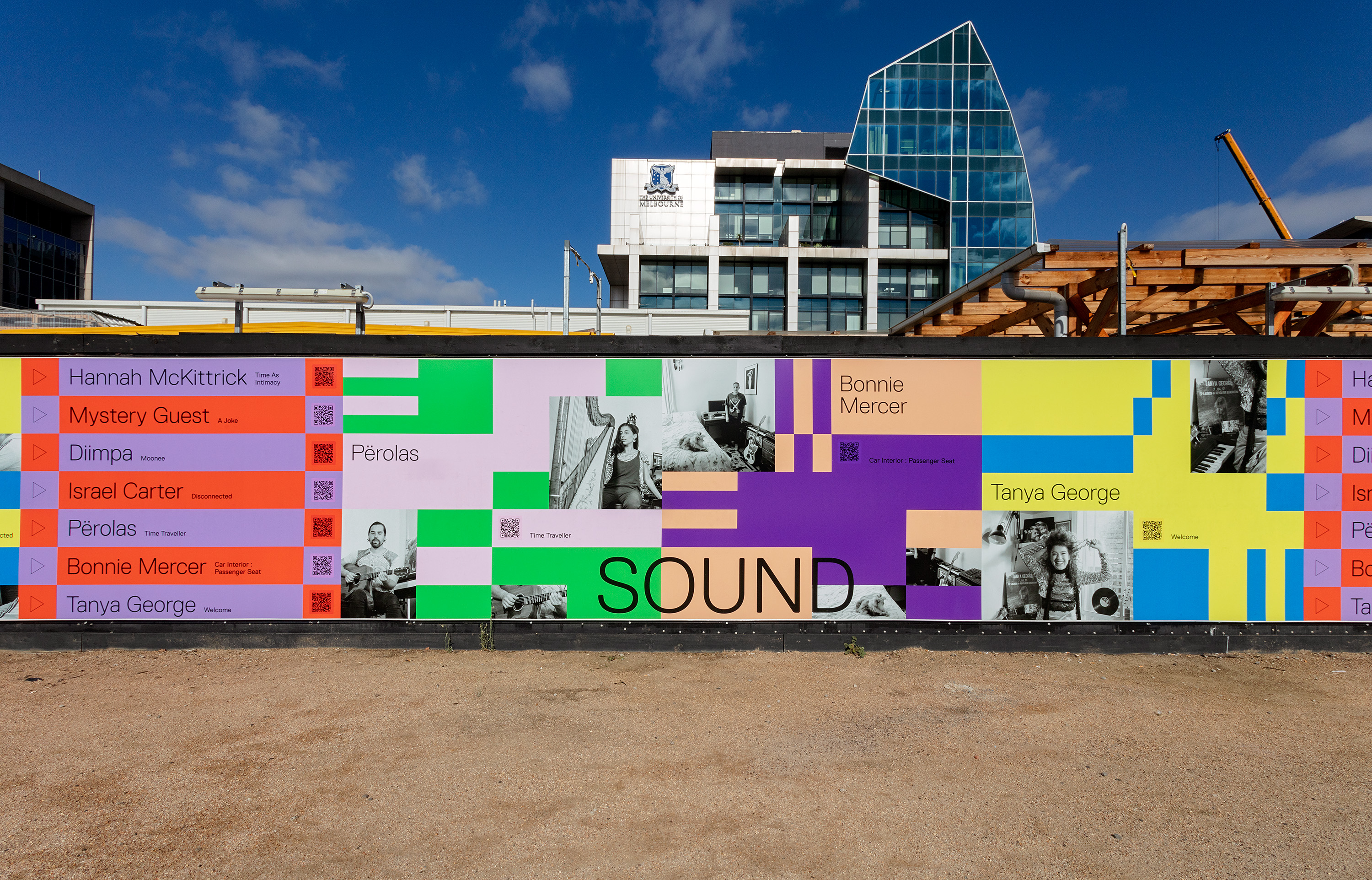 A mural featuring images of musicians and blocks of colours covers construction hoarding in a plaza.