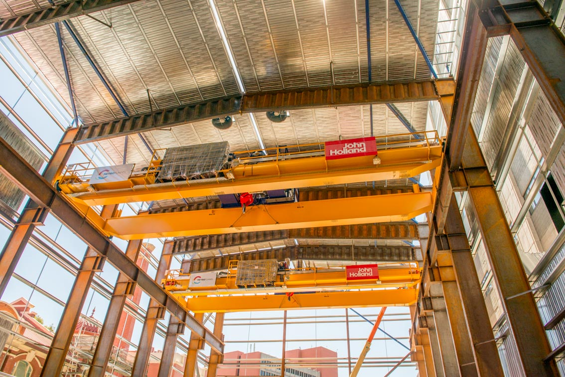 Gantry cranes with John Holland and Metro Tunnel signage inside the Franklin Street acoustic shed.