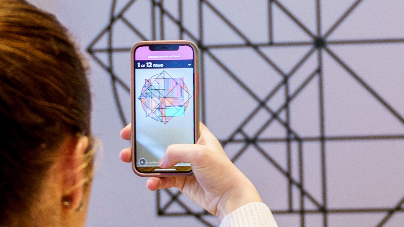 A person holds a phone camera up to an artwork and the image is different on the phone screen