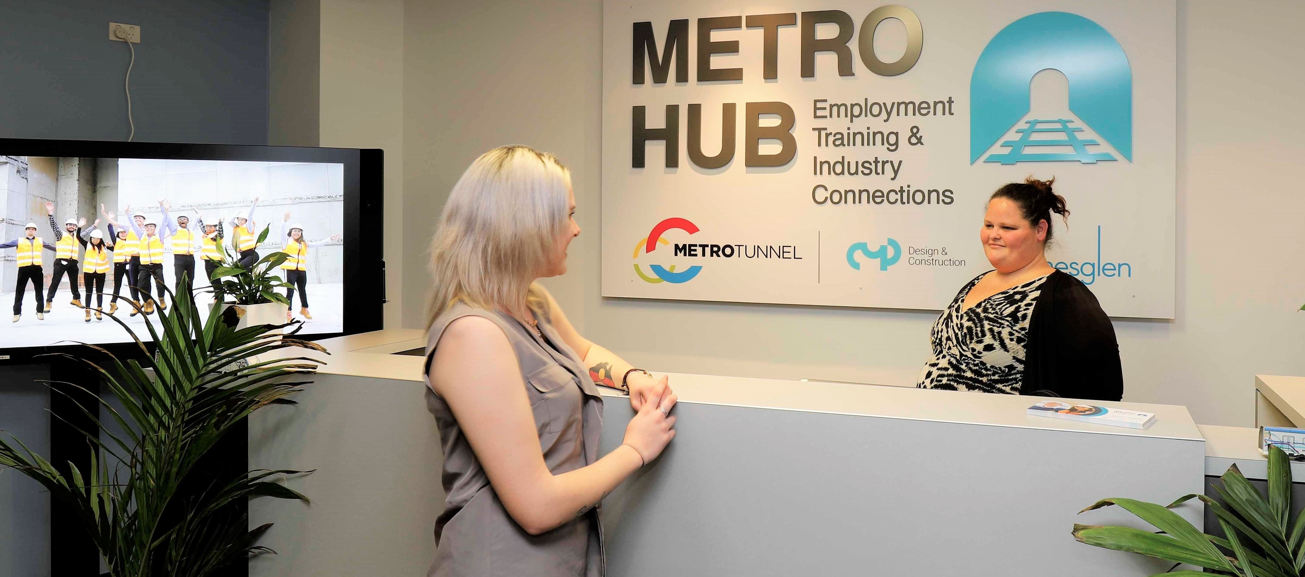 A woman speaks to another woman behind a counter with sign on the wall behind that says 'METRO HUB: Employment Training & Industry Connections