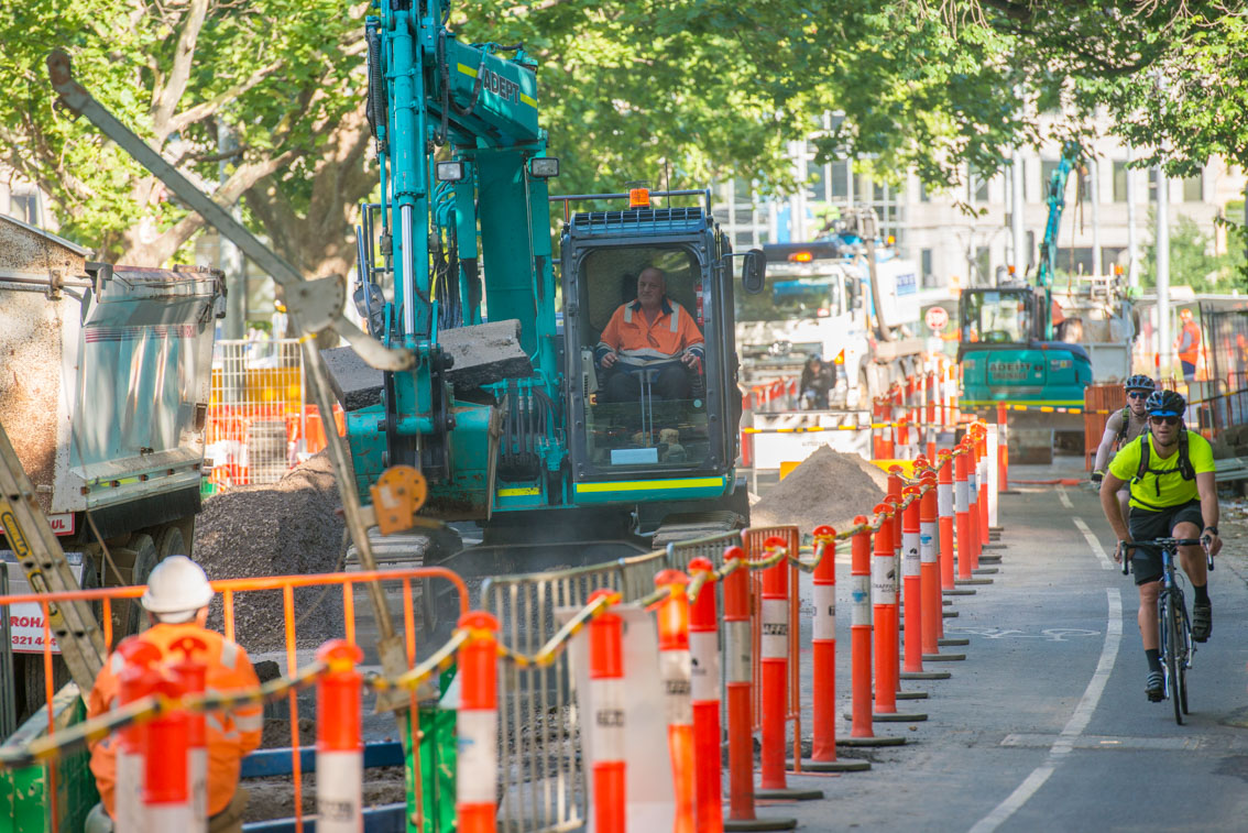 Cyclists passing by excavation works on St Kilda Road.