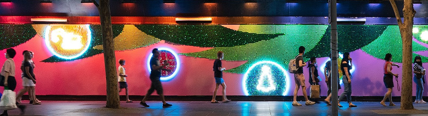 People walk past a neon-lit mural showing Christmas trees and digging machines.