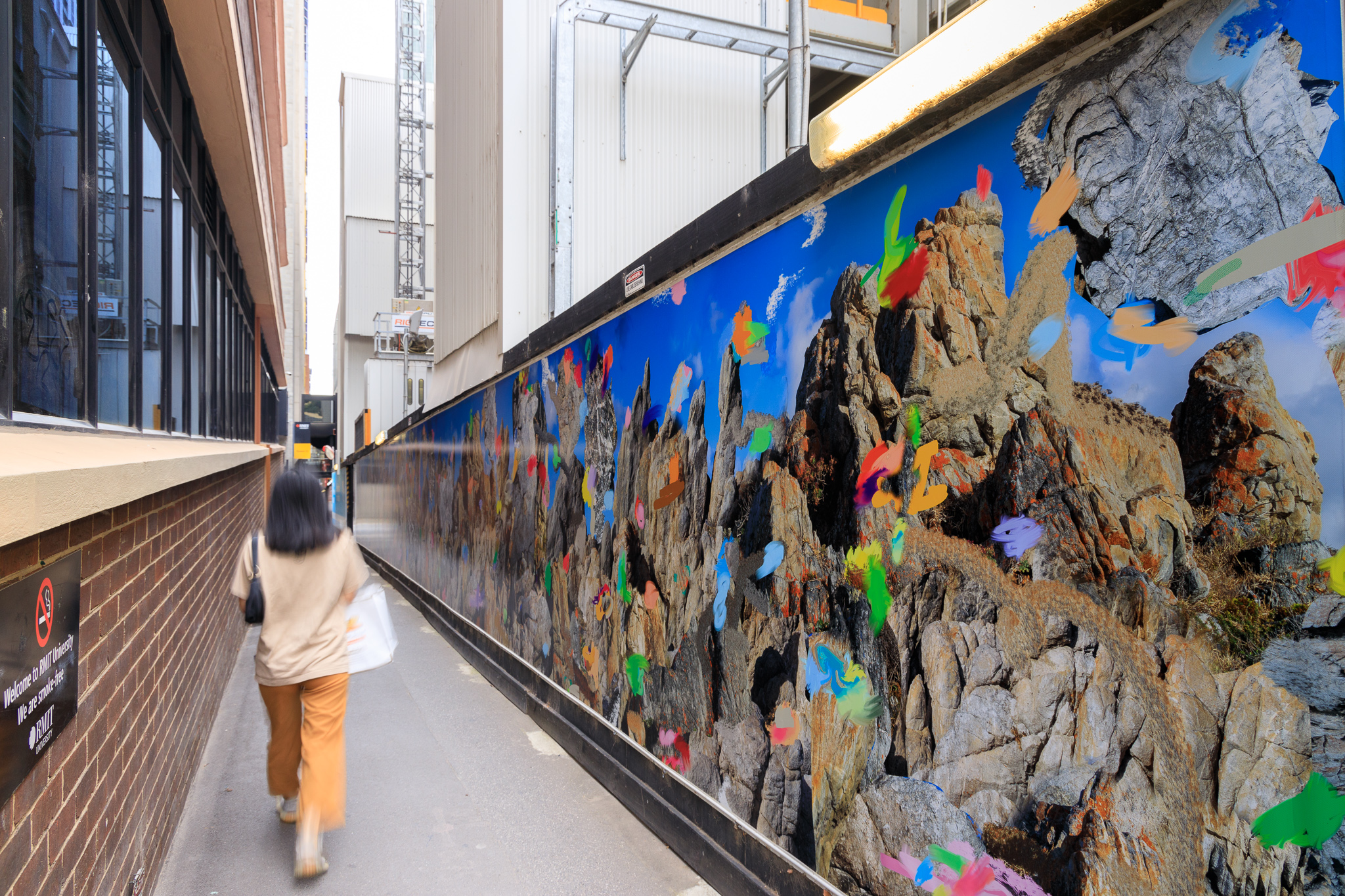 A woman walks past a photographic mural featuring big rocks and coloured flecks