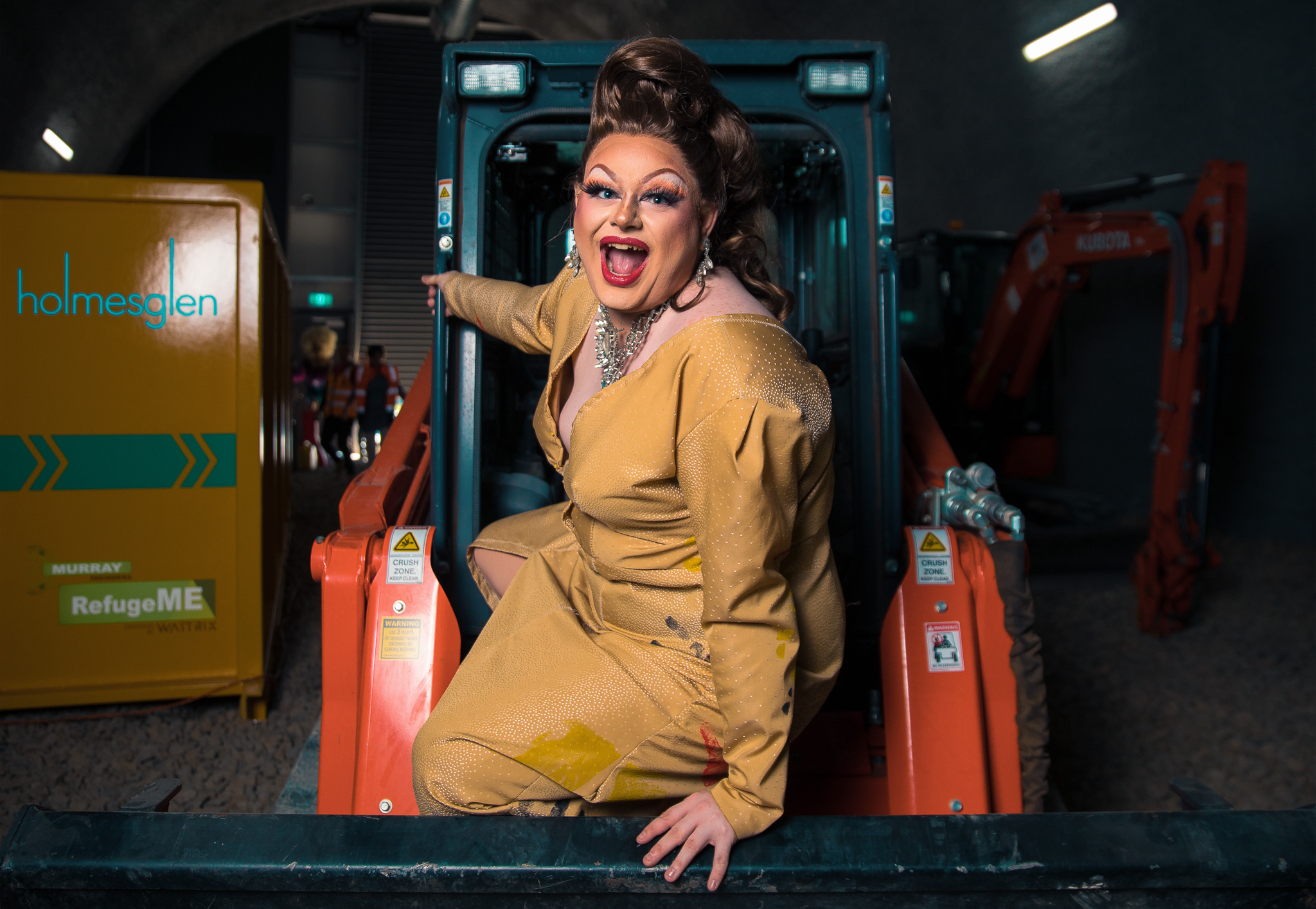 A drag queen poses in front of construction equipment in a tunnel