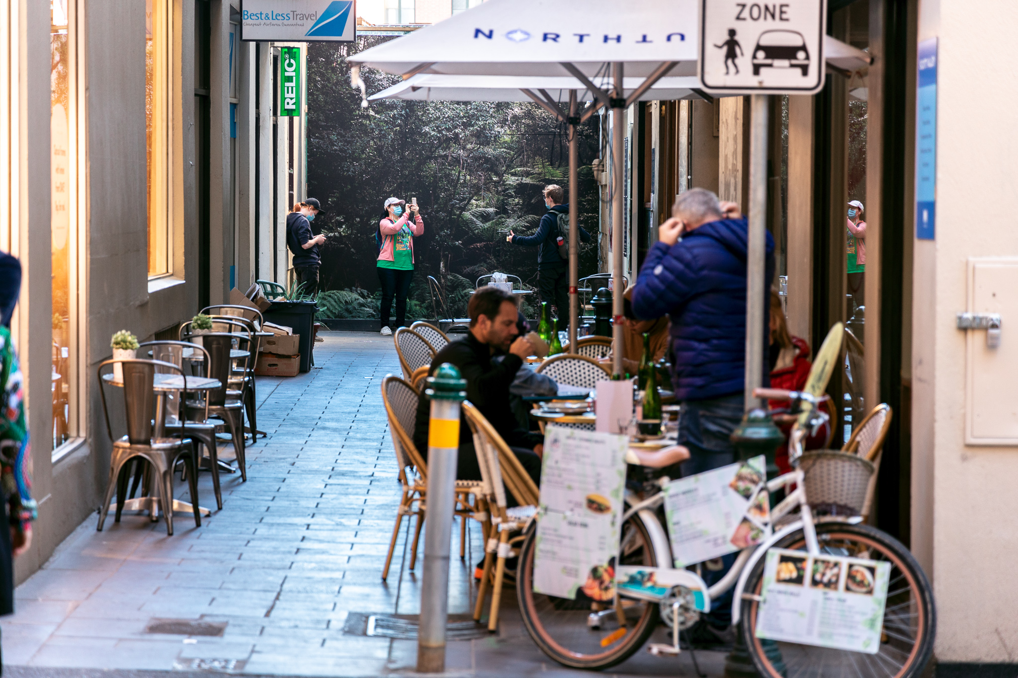 People dine in a laneway in front of an artwork