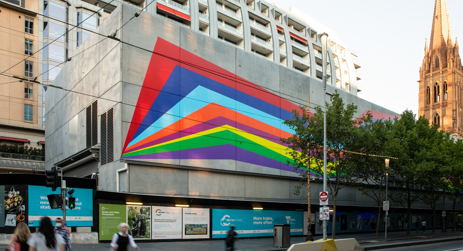 A large concrete shed on next to a busy road with a colourful artwork on the side