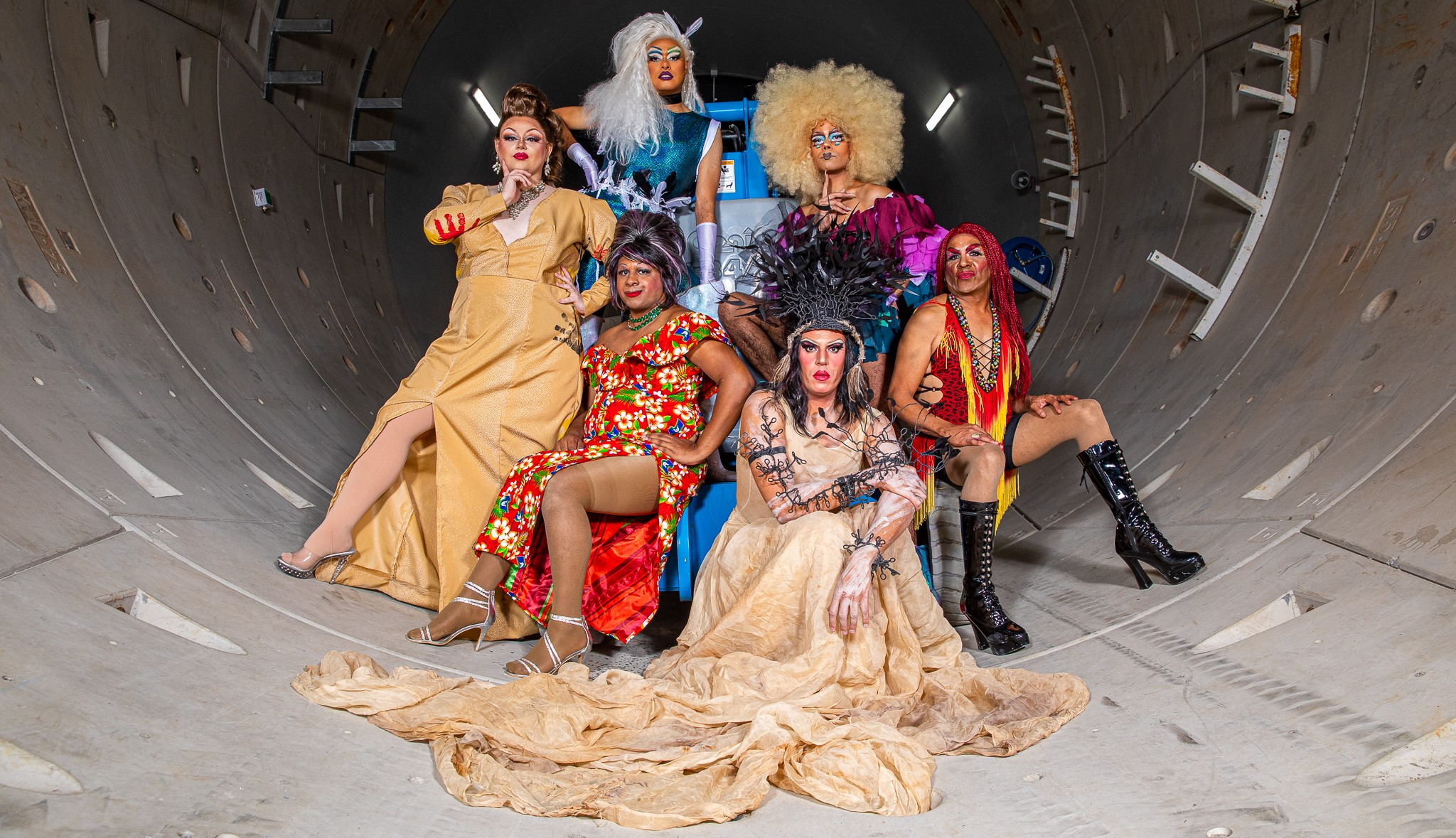 Six Indigenous drag queens pose in front of construction equipment in a tunnel