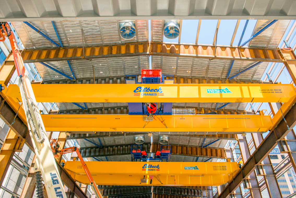 Three yellow gantry cranes and elevating work platforms inside the Franklin Street acoustic shed.
