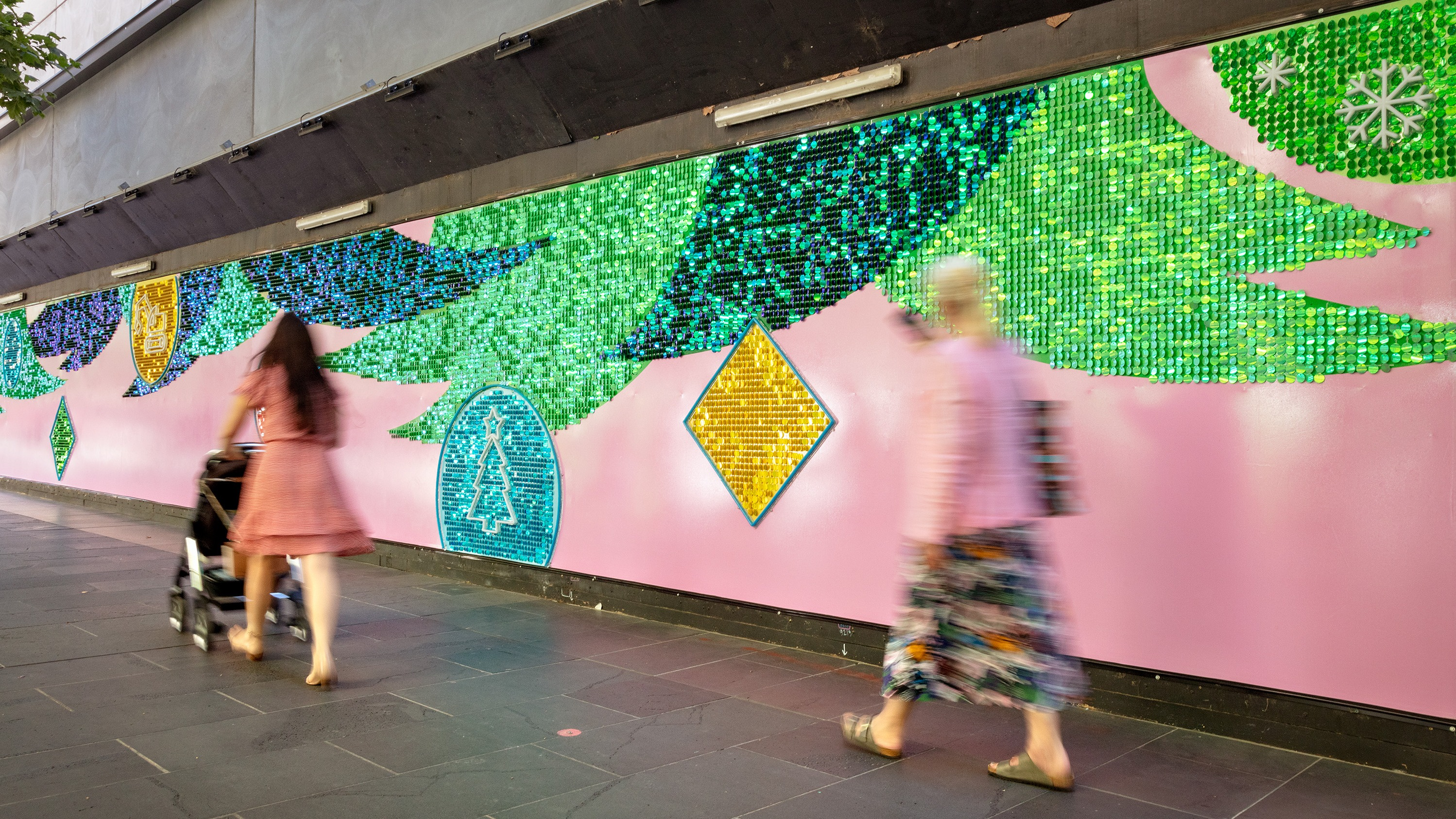 People walk past a colourful mural with shimmering Christmas trees.