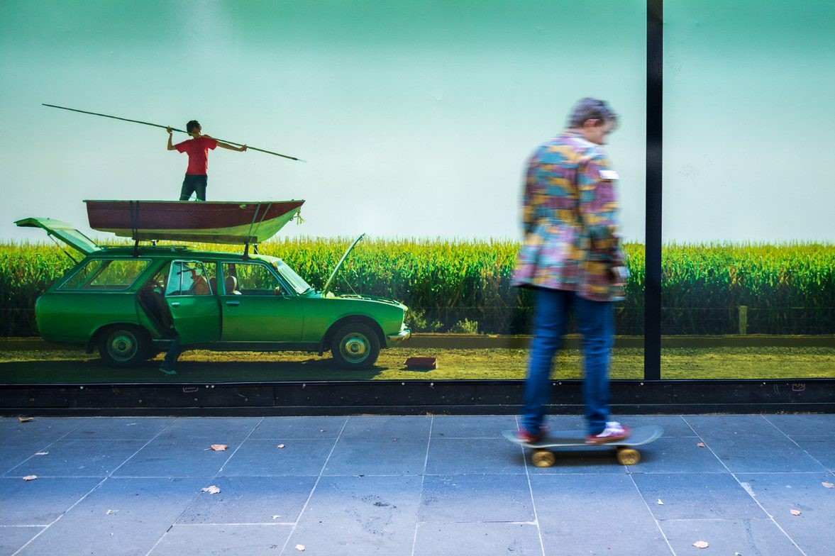 A man in a colourful jacket skateboards past an image of a man holding a spear in a boat on top of a car.