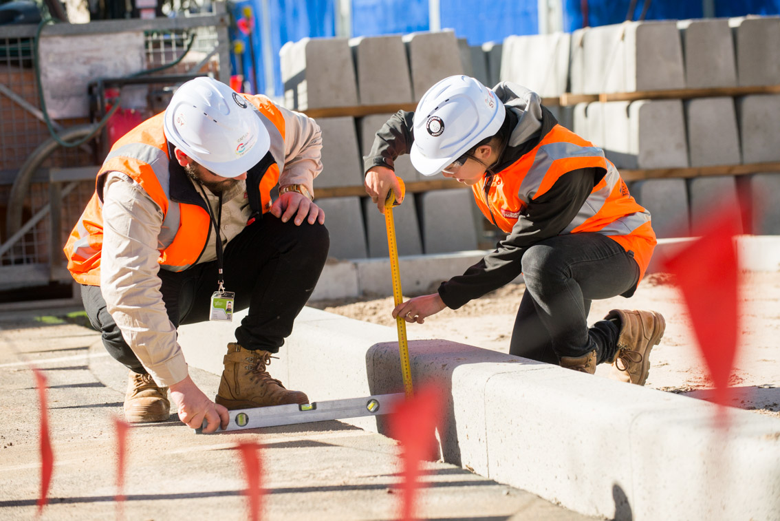 Two workers measuring concrete slabs at a Parkville worksite.