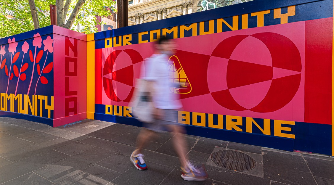 A person walks past temporary outdoor walls painted in blue, gold, pink and red with the words 'NOLA' and 'Our community, our Melbourne