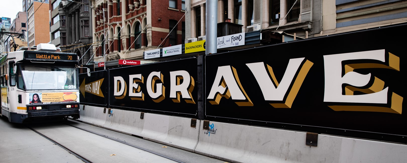 Old-fashioned signage points to Degraves Street behind tram tracks.