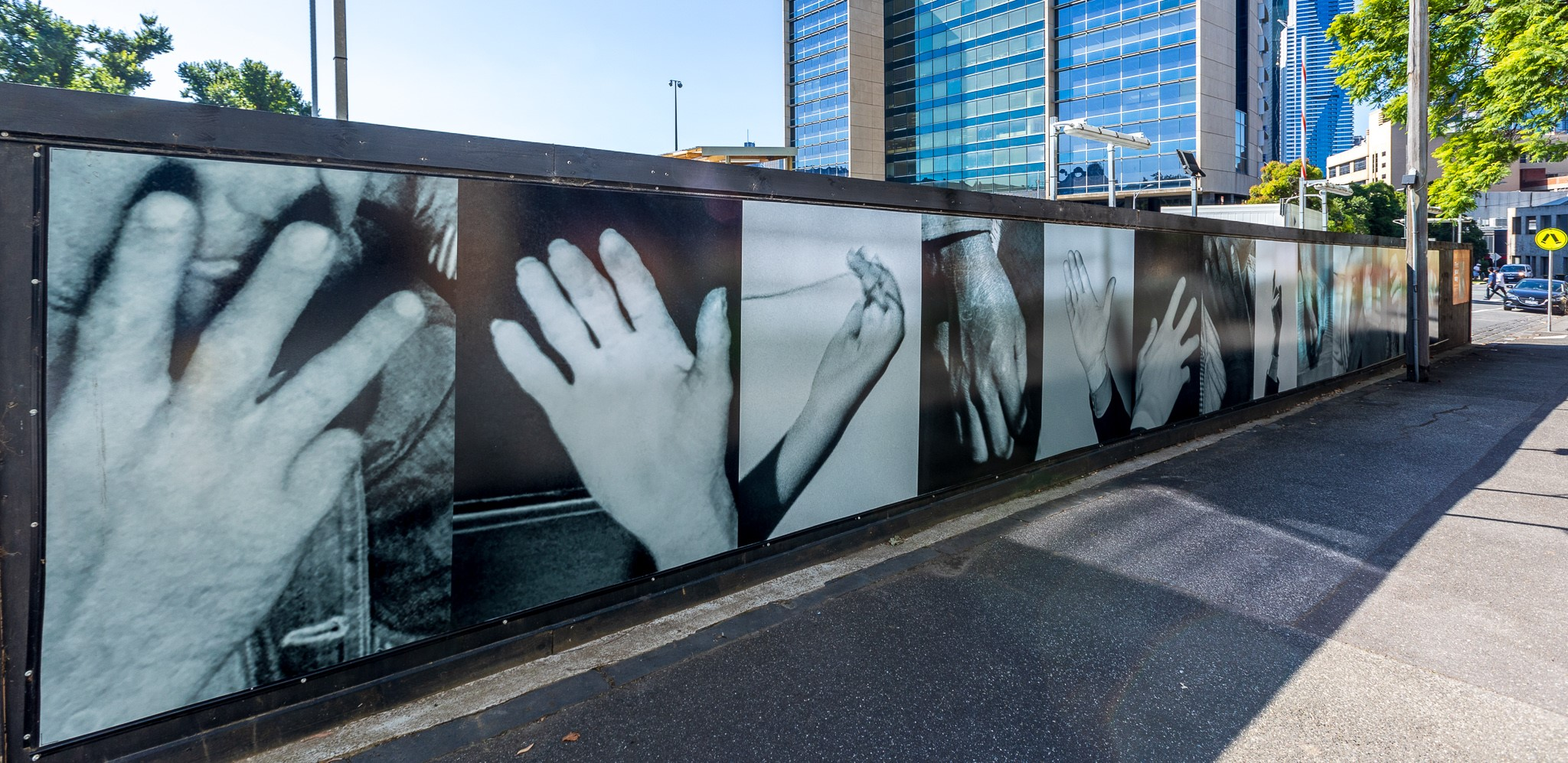 Large black and white photographs of hands along a wall