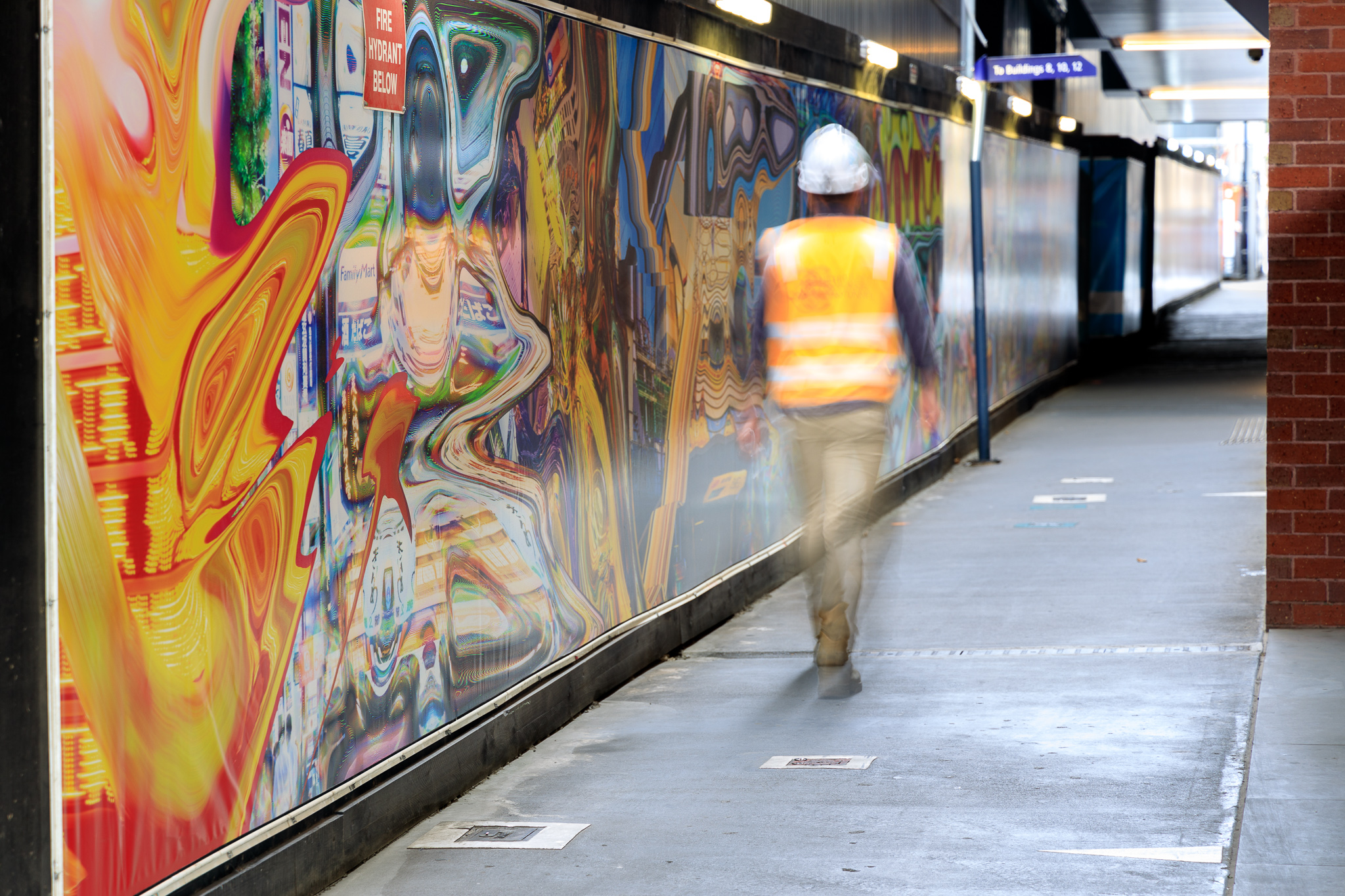 A person in a hard hat and hi-vis walks past a colourful and distorted image on a wall